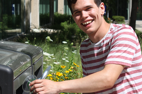 Student recycling a plastic #1 cup in one of the outdoor solar compactor recycling bins