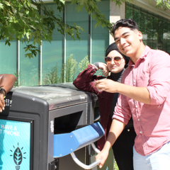 Students recycling #1 plastic PET in the outdoor Big belly solar compacting recycling container.