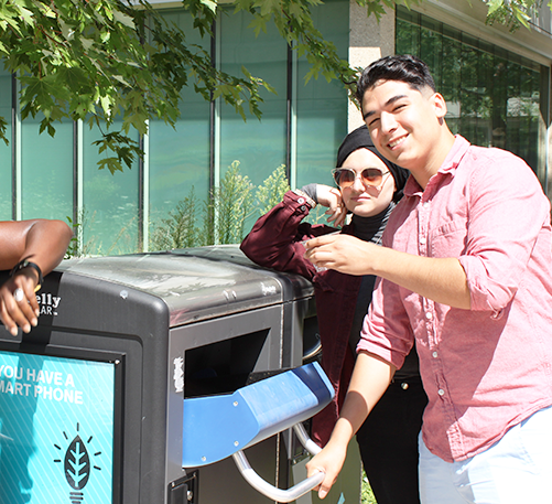 student recycling a plastic cup in the bigbelly.