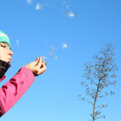 student scattering seeds in the prairie
