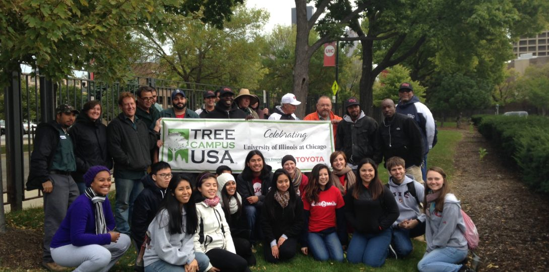 UIC staff and students hold up the Tree Campus USA banner during an OAKtober tree planting event
