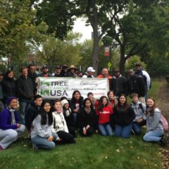 group of UIC staff and students surround the UIC Tree Campus USA sign