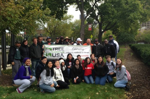 Grounds crew members and student volunteers pose with the Tree Campus USA banner after a day of tree planting.