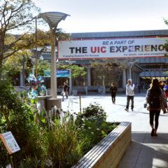 students walking on campus under UIC Experience banner next to a satellite garden Photo: Julie Jaidinger