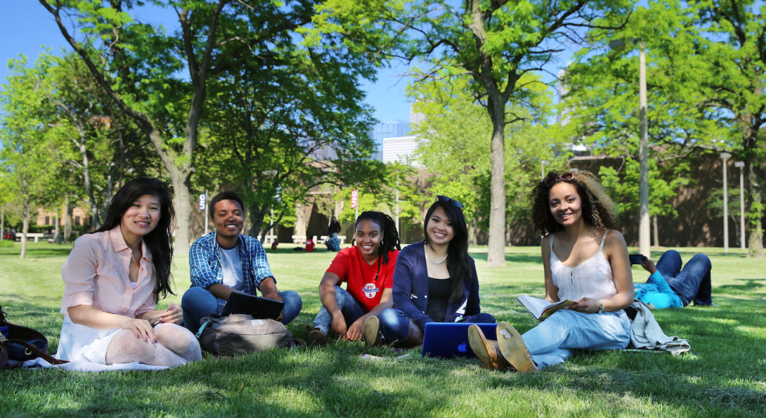 Students sit on grass underneath trees