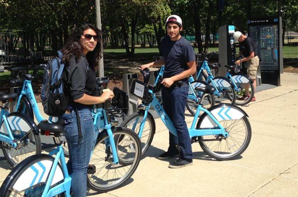 students riding baby blue Divvy bikes