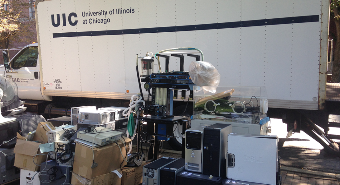 UIC moving truck behind a pile of old university electronics
