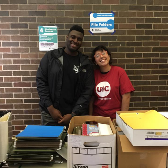 Eco-Educators help organize boxes of file folders at the Great Stuff Exchange event