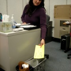 Office working placing paper in her office recycling bin