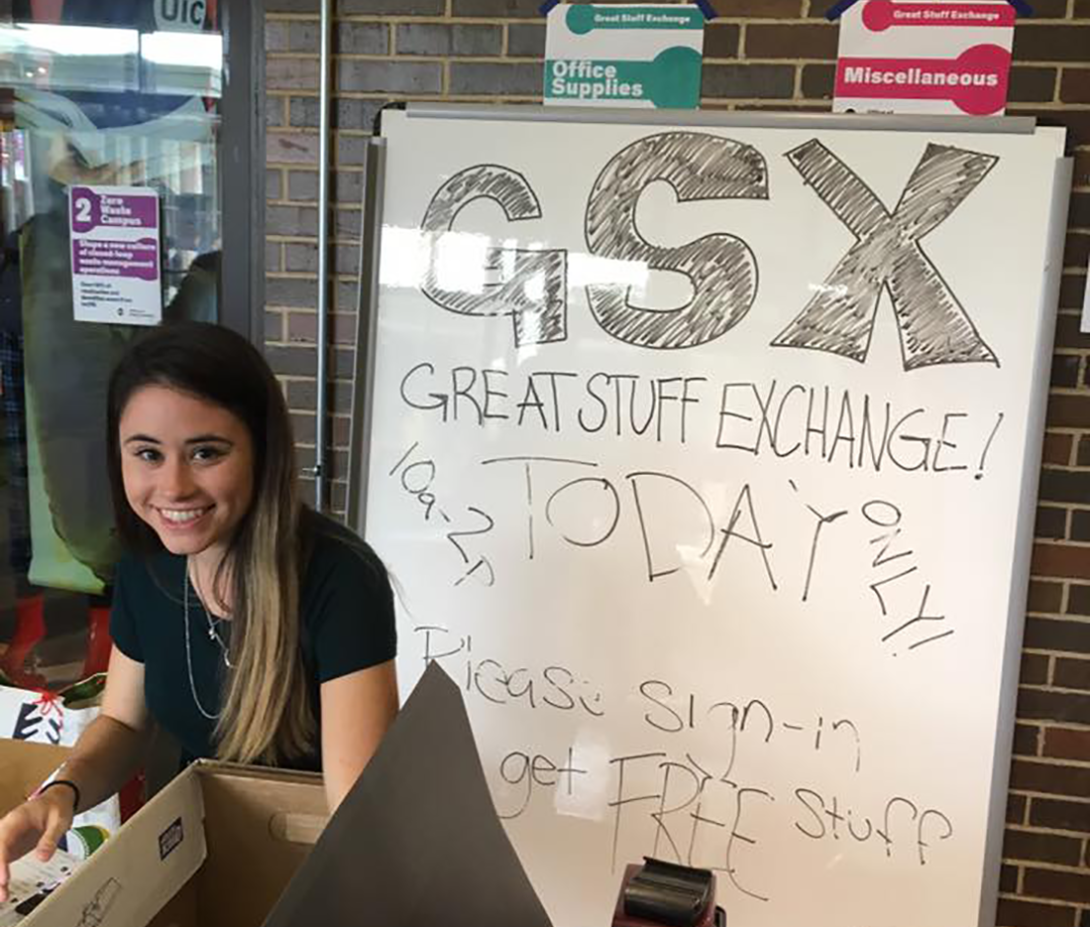 student volunteer helps at the Great Stuff Exchange - sitting in front of a sign that reads,