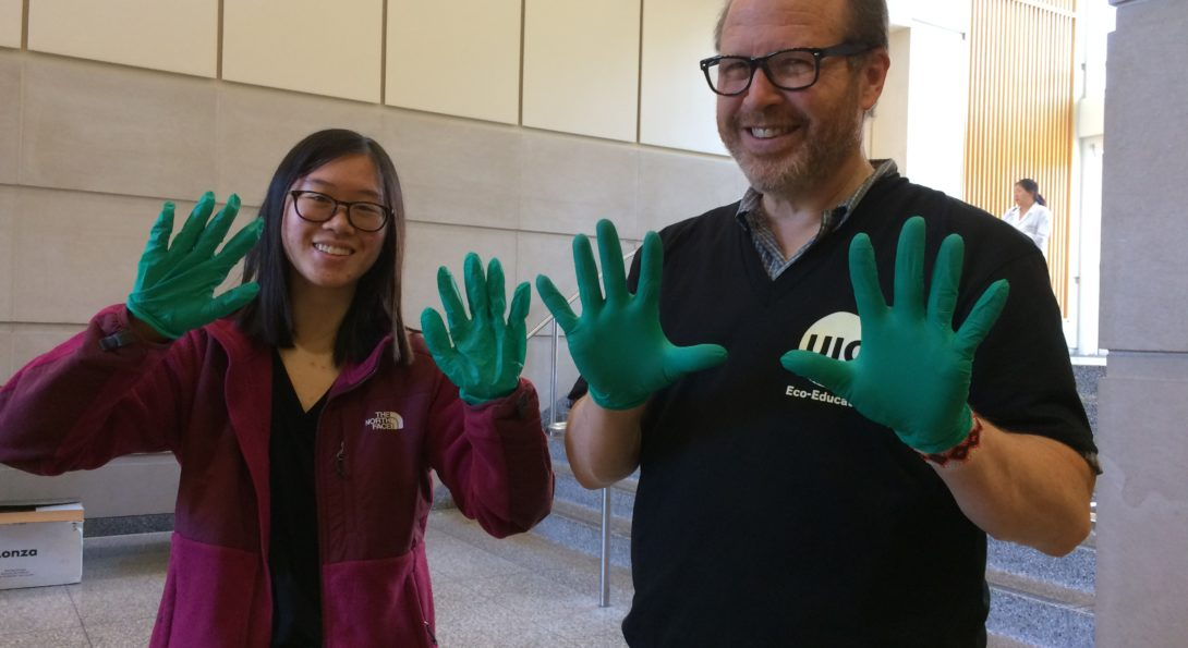 Recycling Coordinator and student recycling intern show off green nitrile gloved-hands