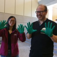 staff and student hold up their hands in green nitrile gloves
