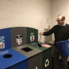 UIC Staff empties his desk-side recycling bin into the larger hallway bin