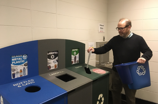 Recycling Coordinator, Joe Iosbaker places waste paper into the paper recycling bin in the hallway