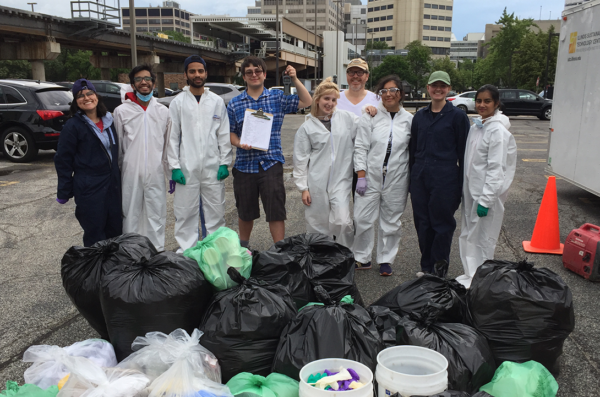 Students wearing white safety coveralls stand in front of piles of recycleables and trash during teh 2017 UI Health waste audit