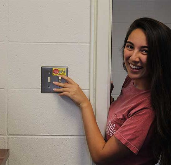 student turns off lights as she leaves the room