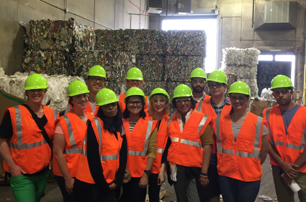 Students in hard hats and orange safety vests stand in front of 20-foot bales of paper to be recycled