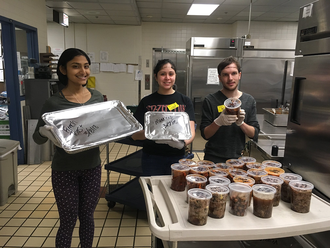 students show off 2 trays and 25 1-quart containers of donated food