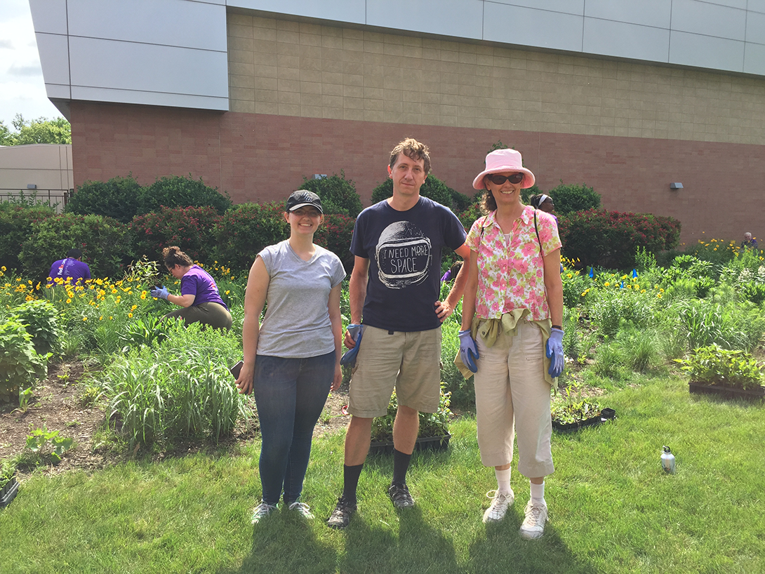 volunteers pose, shovels and gardening gloves in hand in front of the prairie garden