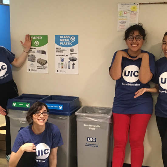 Eco-Volunteers stand by recycling bins inside a UIC building