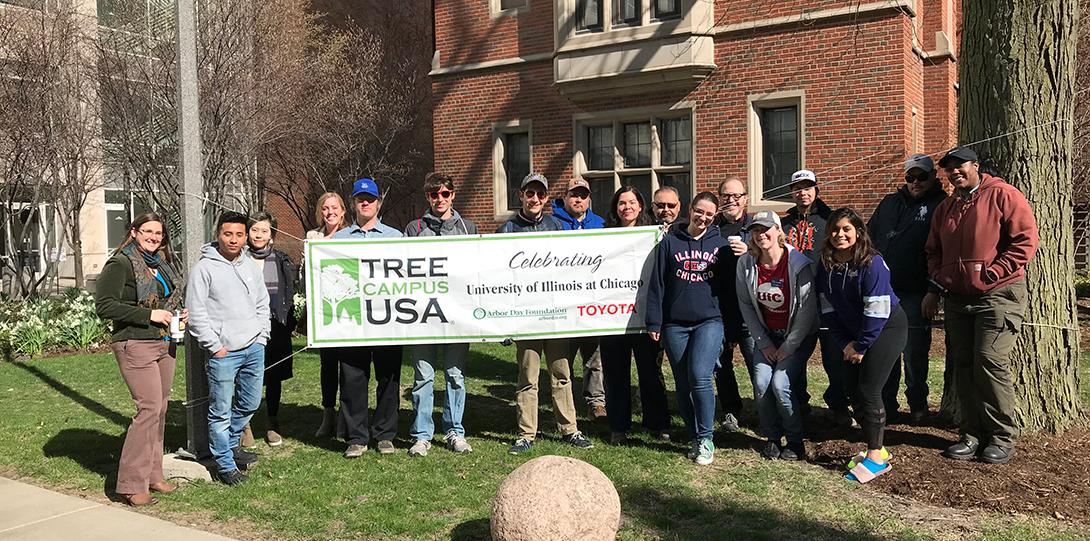 UIC staff and students hold up the Tree Campus USA banner during the College of Medicine tree planting event