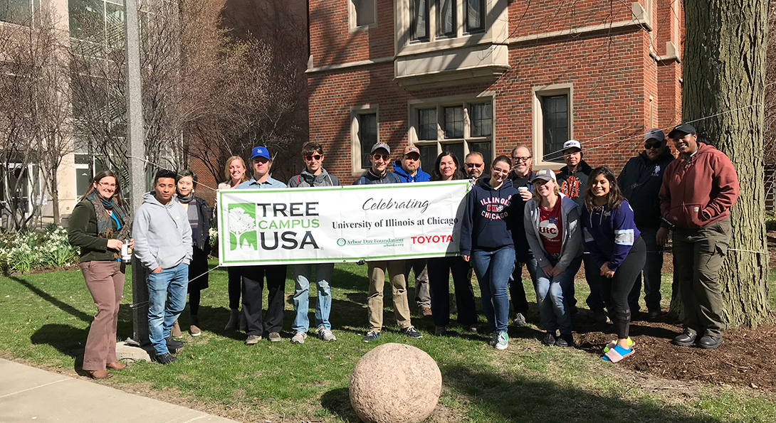 volunteers and tree enthusiasts stand by the Tree Campsu USA Banner