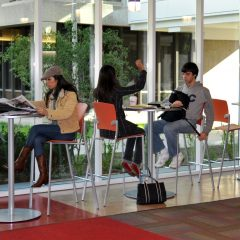 students sit on high boy tables and chairs in the lobby next to floor-to-ceiling windows