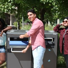 Student using the outdoor recycling bin on campus