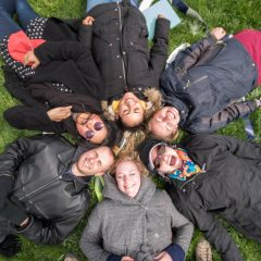 UIC Faculty, staff, and students lay in a circle on top of the geothermal well field