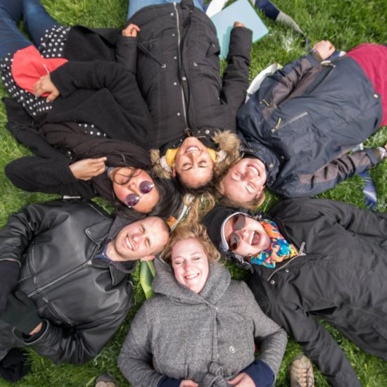 people laying down in the grass, smiling
