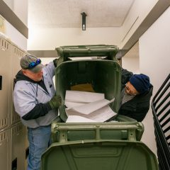 UIC Staff transferring paper to a green tote