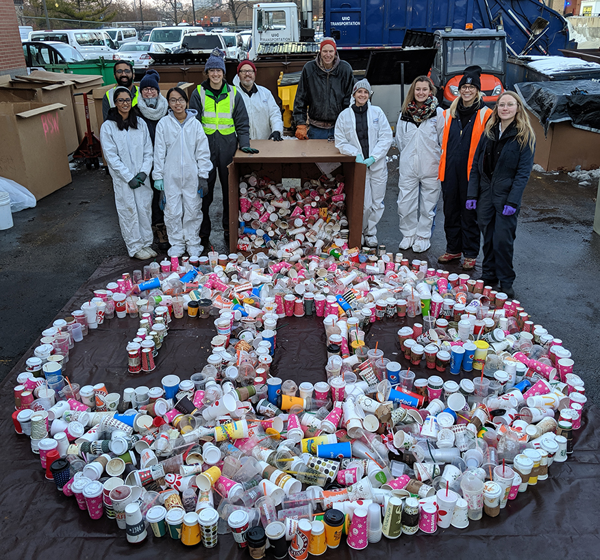 waste audit volunteer stand over thousands of disposed single-use beverage cups designed to look like the UIC logo.