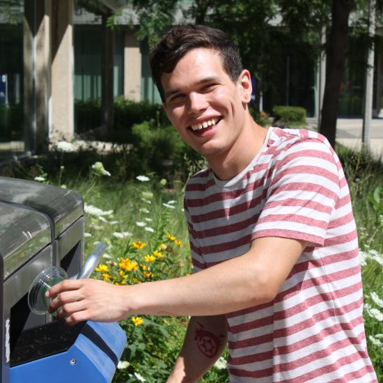 student recycling plastic cup in the outdoor Bigbelly recycling bin