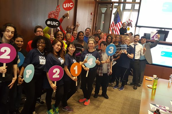 UIC staff hold up their favorite climate commtiment in teh Chancellor's conference room in 2850 UH.