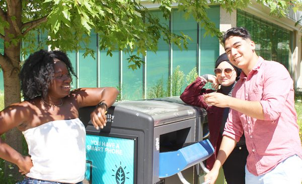 students recycling in outdoor bin
