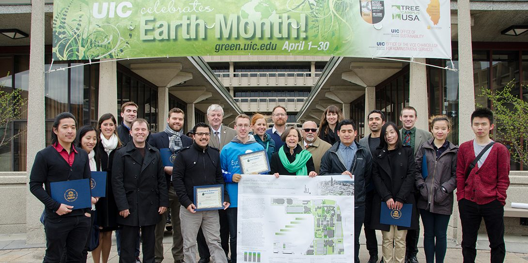 Chancellor, students and faculty underneath a UIC Earth Month Banner holding awards