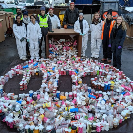 volunteers in hazmats suits stand behind a design they made using all of the disposable beverage cups found in the 2019 waste audit: the UIC circle logo.