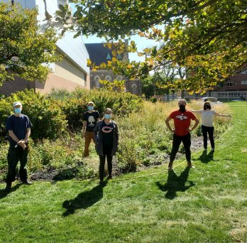 volunteers stand more than 6 feet apart with masks on ready to do work in the prairie garden