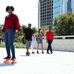 student skateboarding across the Peoria Street Bridge