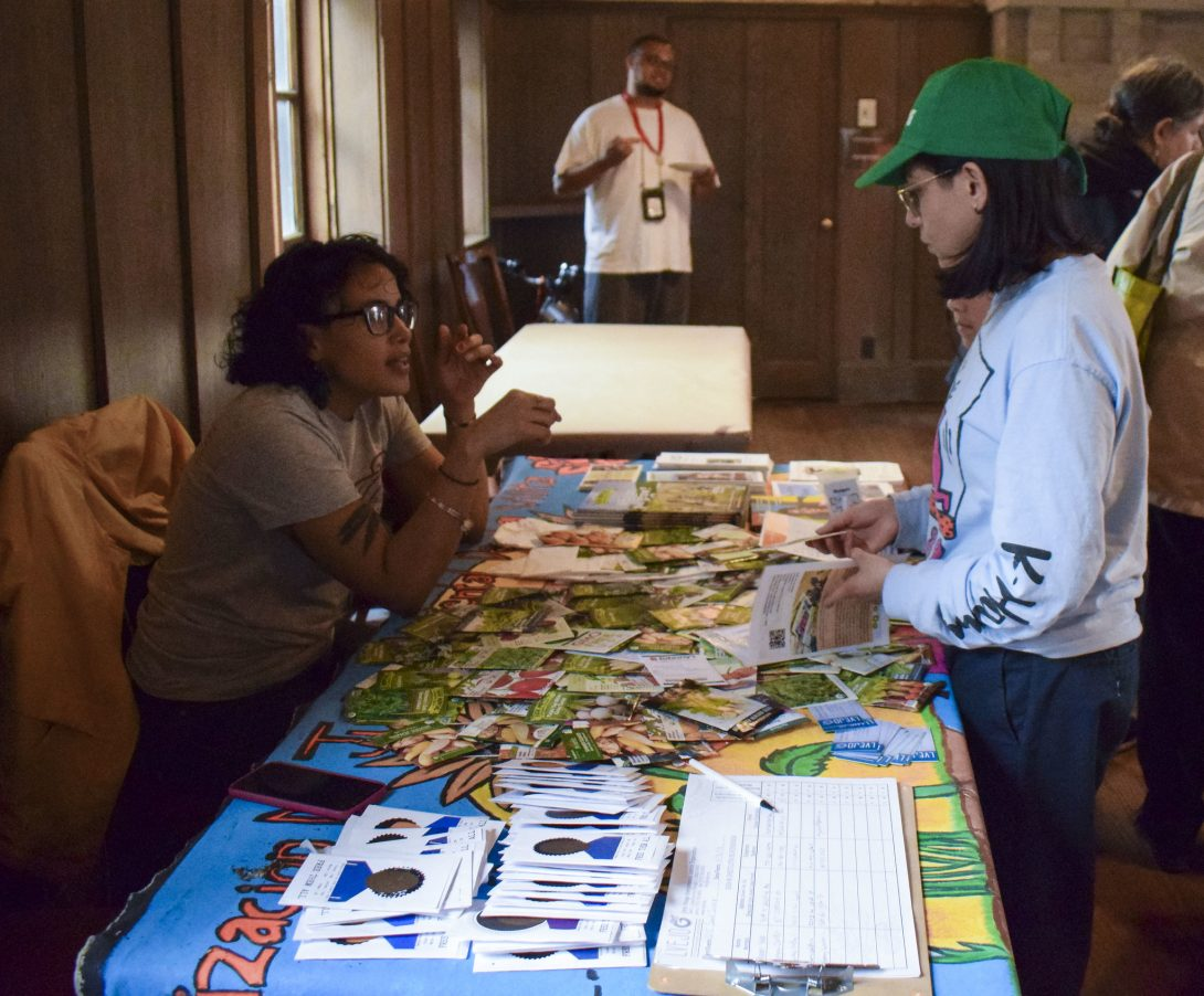 At the Seed Swap event in 2019, a student has a conversation with a person behind a table. Educational literature like brochures and pamphlets cover the table.