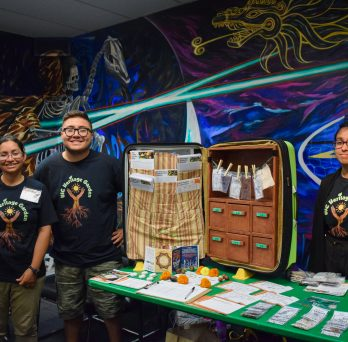 three members of the UIC Heritage Garden stand smiling in front of an open suitcase that contains seeds and educational print-outs.